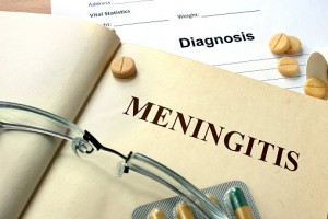 Word Meningitis on a book and pills.