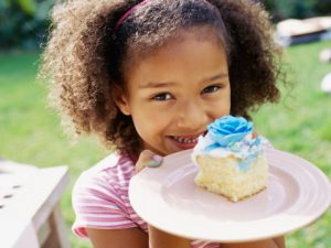 Portrait of a young girl holding a slice of cake