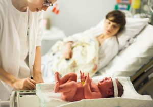 Midwife, mother and newborn baby