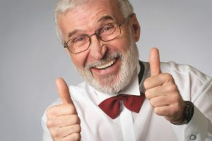 Portrait of a senior man in a tuxedo showing the thumbs up