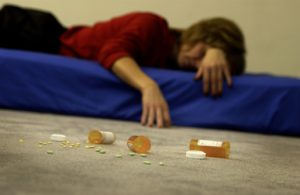Mid adult woman sprawled on a mattress with vials of pills strewn on the floor